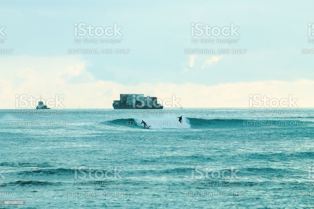 Two paddle boarders catch a wave at Ala Moana Beach stock photo