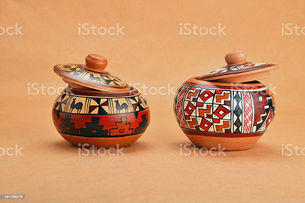 Two painted handmade ceramic pot with lids on kraft paper royalty-free stock photo