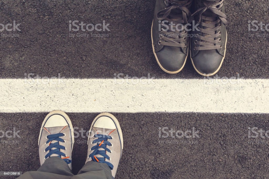 Two pair of sneakers on a asphapt road. stock photo