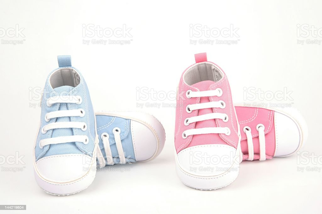 Two pairs of baby shoes, one pair blue and one pair pink stock photo