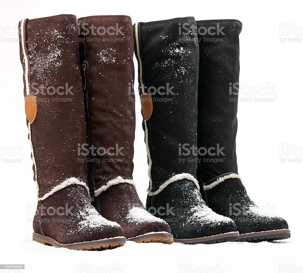 Two pairs of female boots covered with snow stock photo