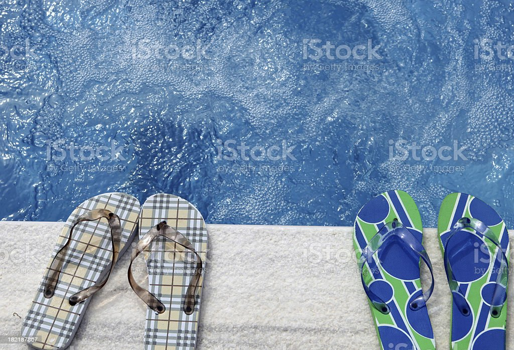 Two pairs of flip flops beside a swimming pool royalty-free stock photo