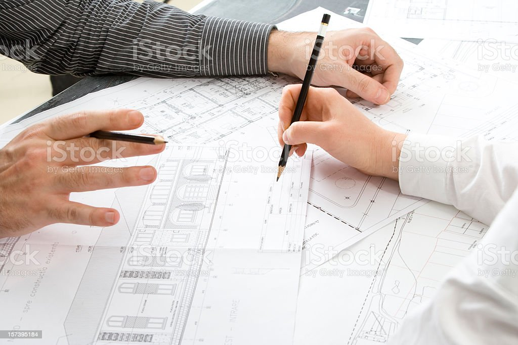 Two pairs of hands working on architectural drawings royalty-free stock photo