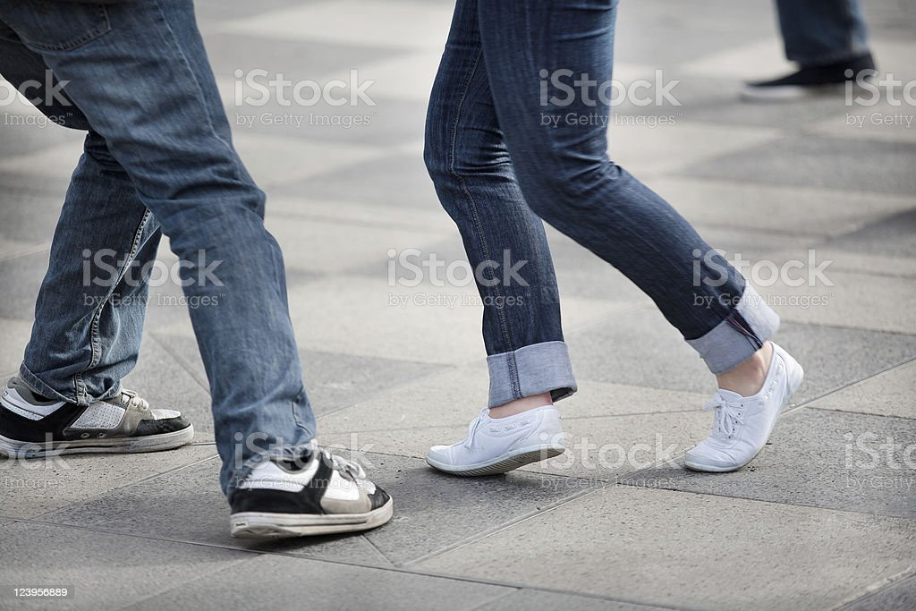 Two pairs of legs dancing on square-tiled pavement stock photo