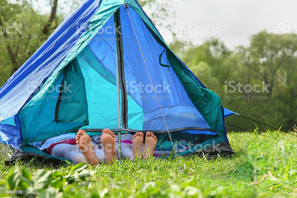 Two pairs of legs stick out from tent on meadow royalty-free stock photo