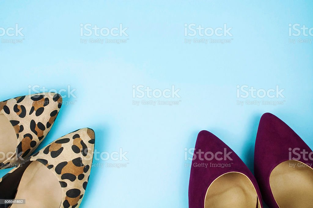 Two pairs of stiletto shoes on light blue background. stock photo