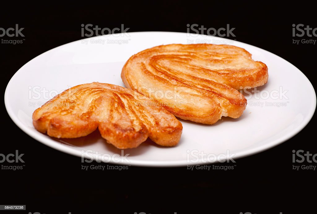Two palmier biscuits with sugar on the white plate close-up stock photo