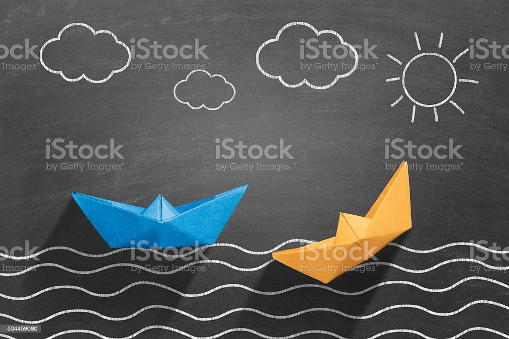 Two paper boats floating on water stock photo