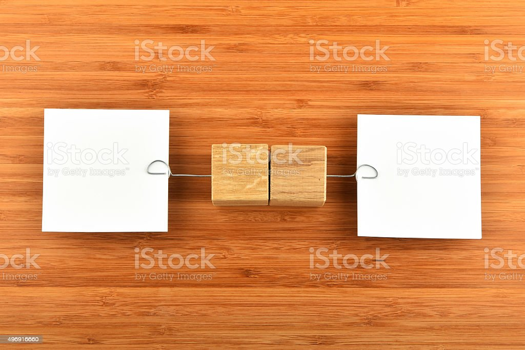 Two paper notes with holders in different directions on wood royalty-free stock photo