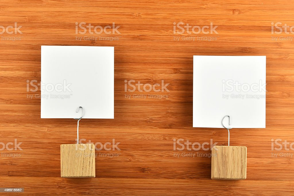Two paper notes with wooden holders on wooden background royalty-free stock photo