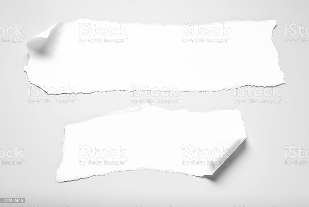 Two paper scraps with curled corners over gray background stock photo