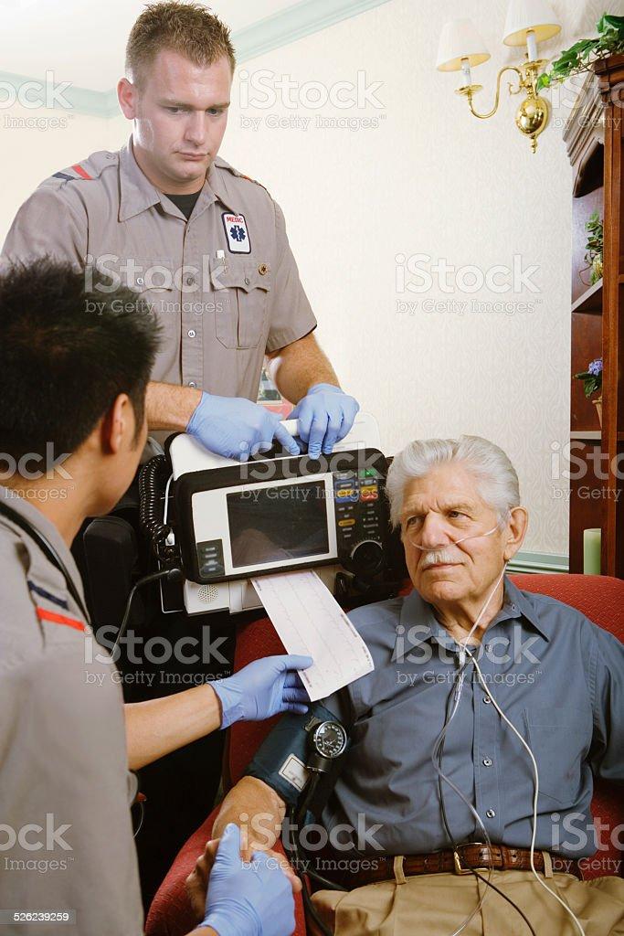 Two paramedics examining senior man with monitor stock photo