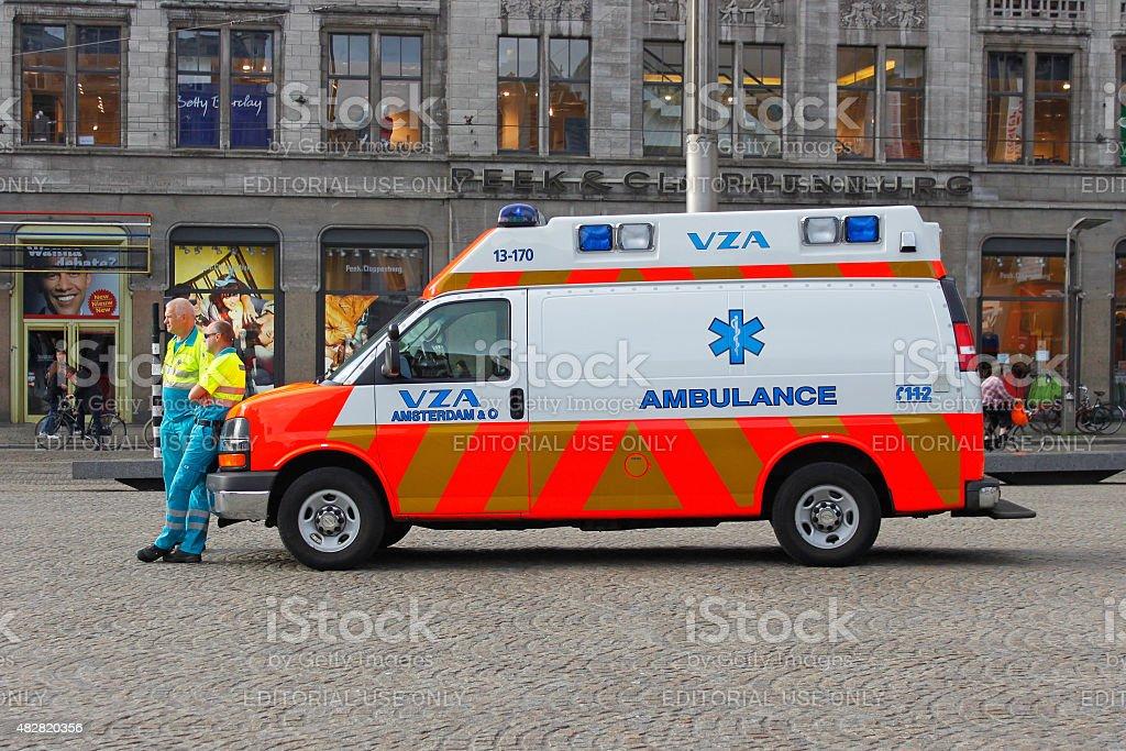 Two paramedics hear their ambulance car. stock photo