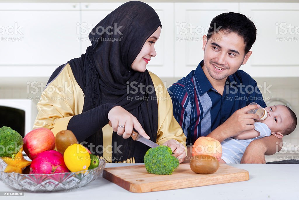 Two parents and baby making healthy food stock photo