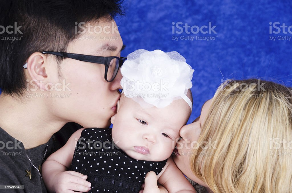 Two parents kissing opposite sides of baby's face. royalty-free stock photo