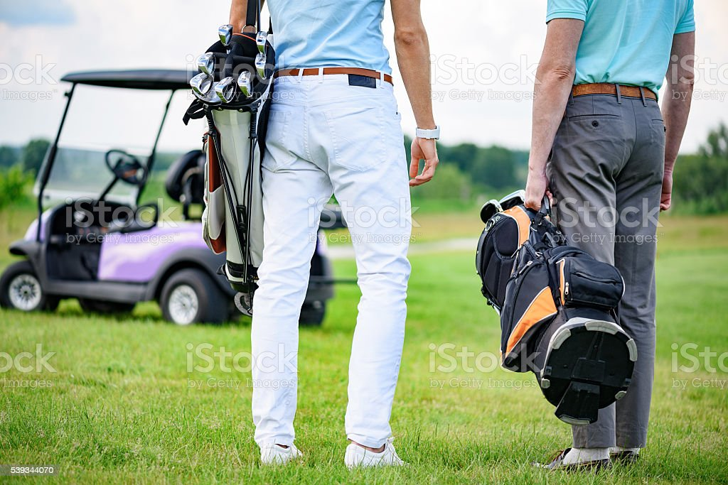 Two partners of game standing on golf course stock photo