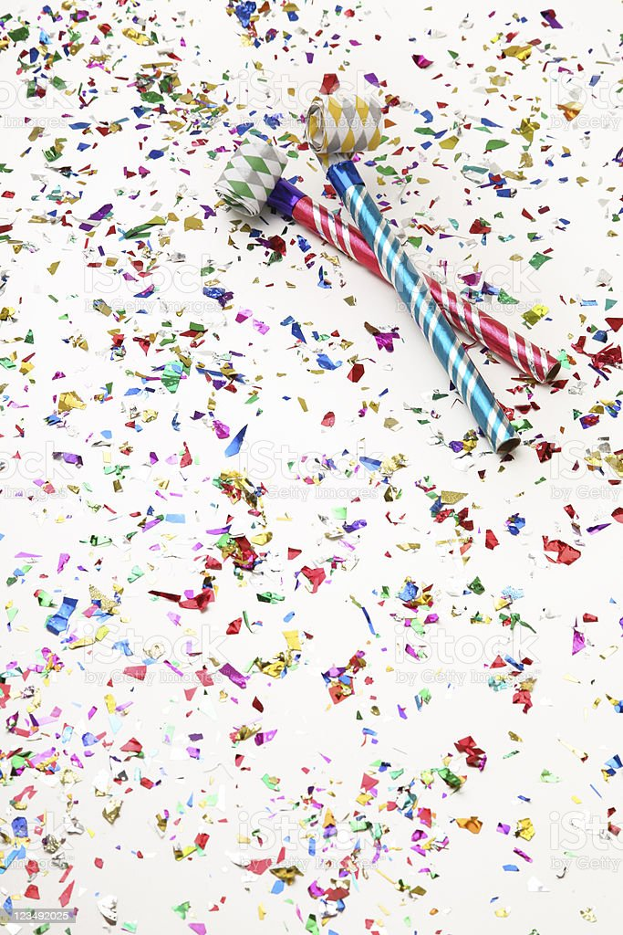 Two Party Horn Blowers Surrounded by a lot of Confetti stock photo