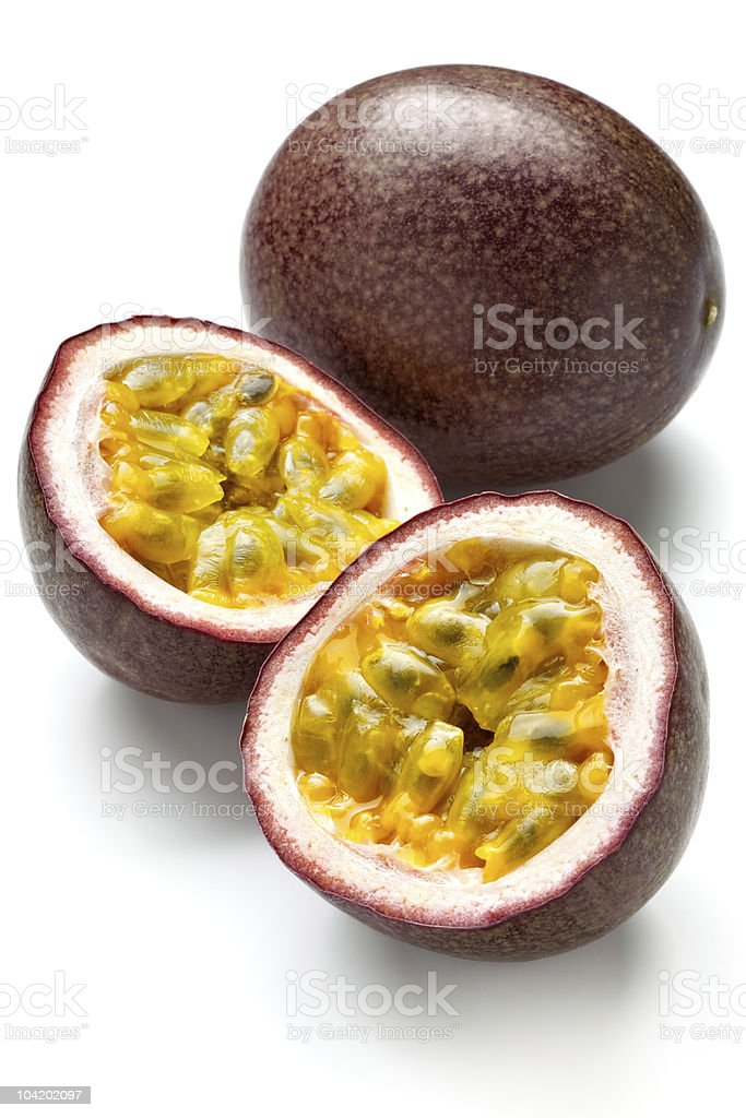 Two passion fruits, one cut in half, on a white background stock photo