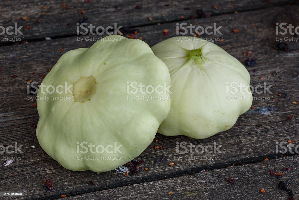 Two pattypan squash lie on the old wooden table in stock photo