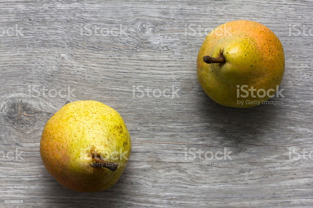 Two pears on wooden table stock photo