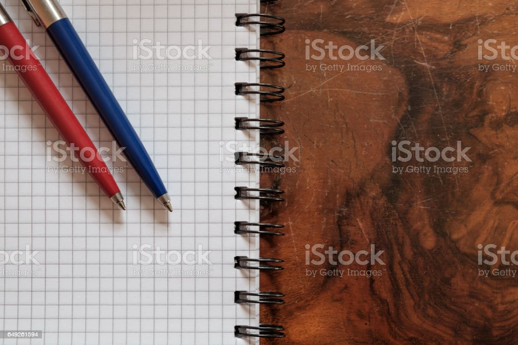 two pens on a copy book isolated on wooden background stock photo