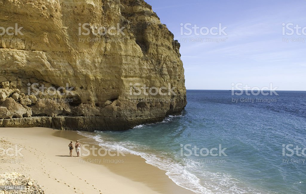 two people are standing on a beach near the cliffside royalty-free stock photo