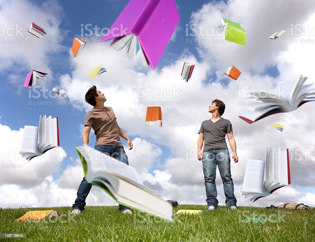 Two people astonished as the sky rains books stock photo
