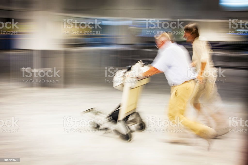 Two people at the airport with a luggage cart stock photo