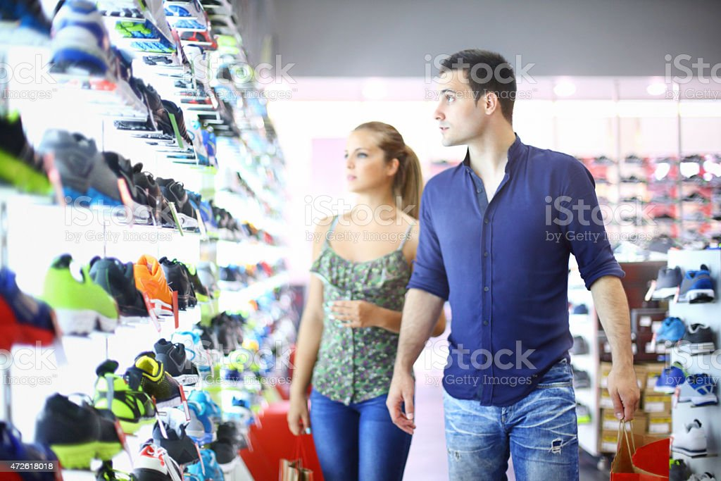 Two people buying shoes in retail store. stock photo