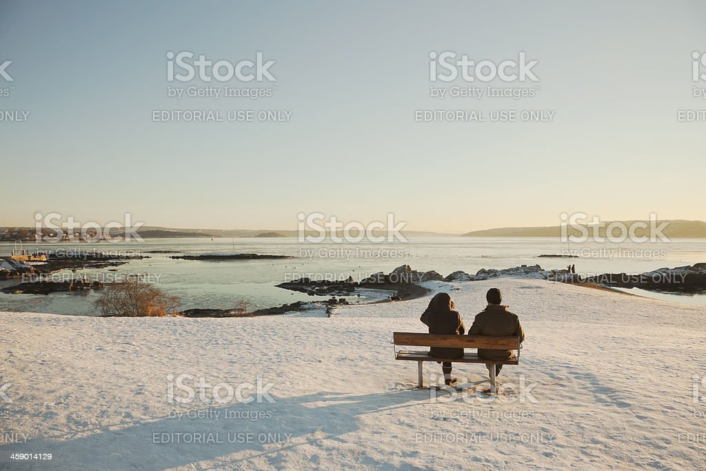 Two people  by the sea  at sunset in January. stock photo