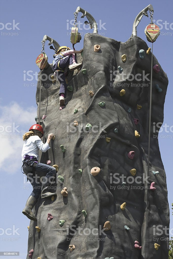 Two people climbing a cylindrical rock wall stock photo