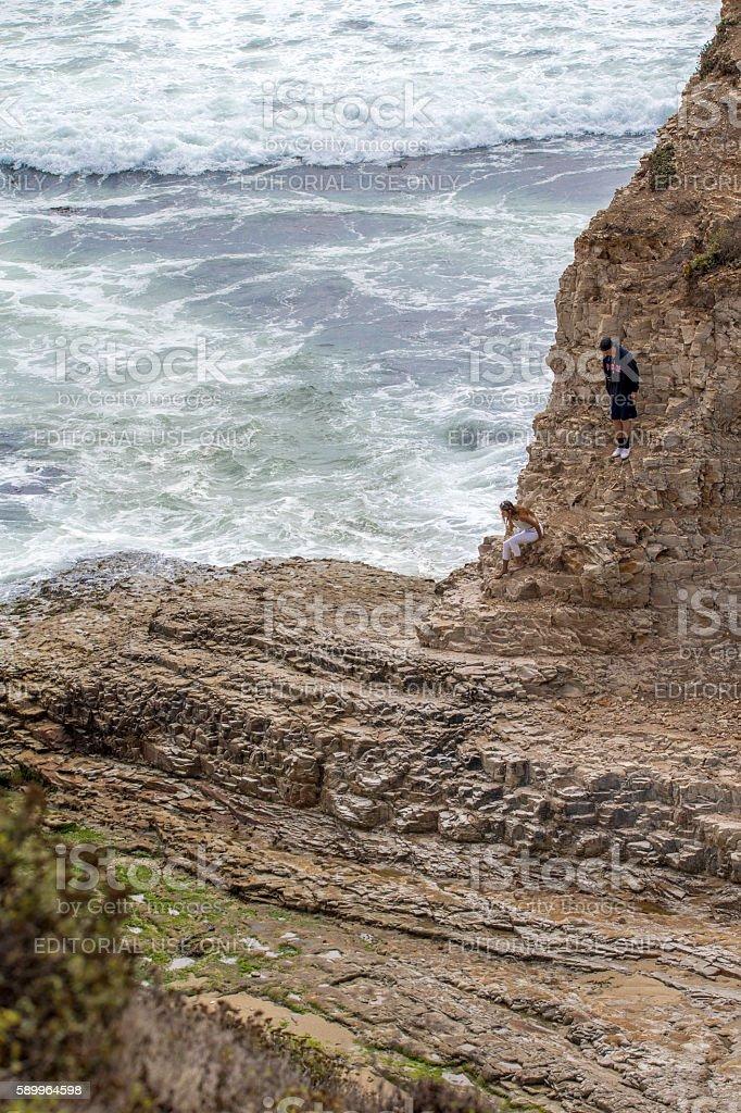 Two people climbing down  at Davenport Beach, Califonia stock photo