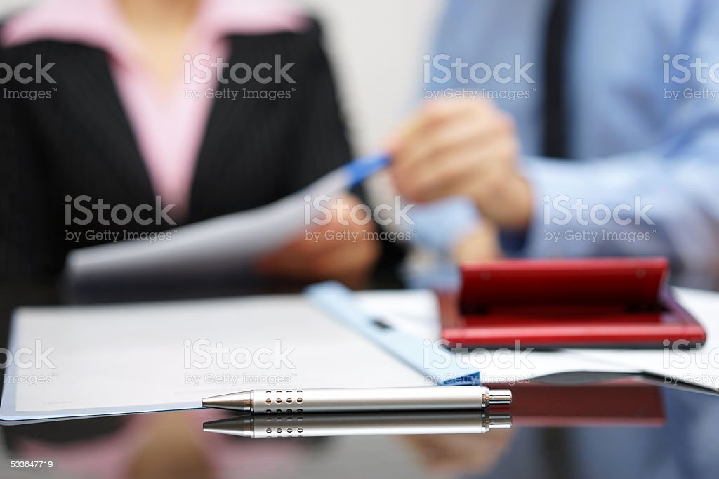 two people discussing about report on meeting with focus on pen stock photo