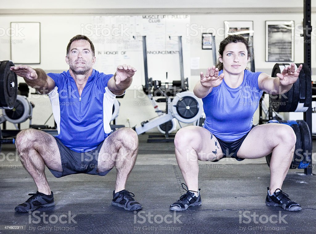 Two People Doing Squats in Gym royalty-free stock photo