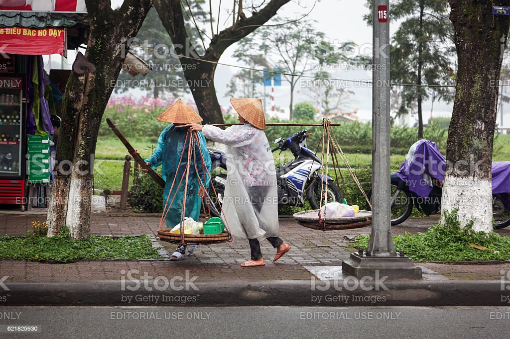 Two people dressed for rain with a yoke stock photo