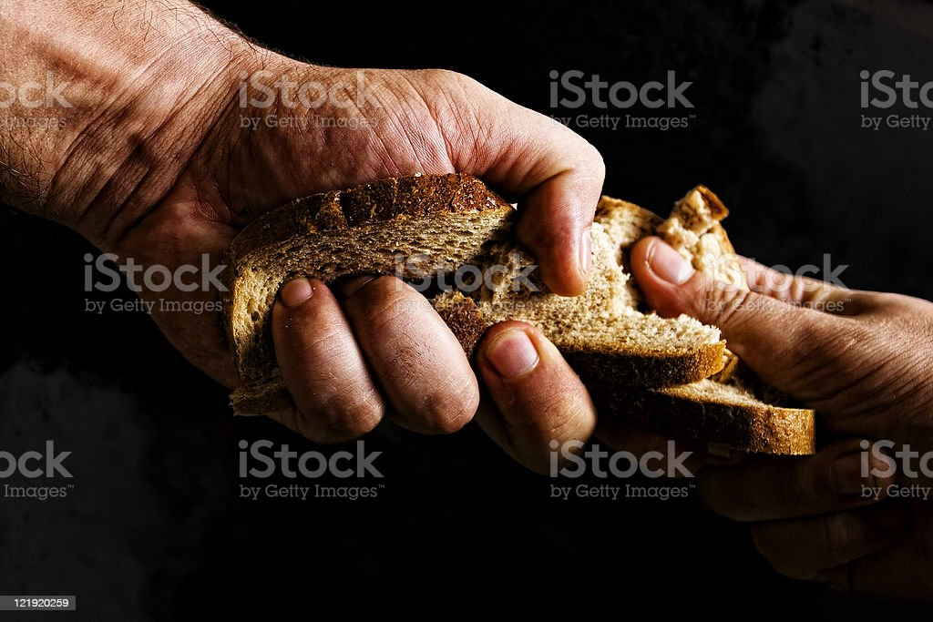 Two people fighting over piece of bread stock photo