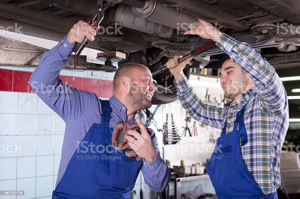 Two people fixing car stock photo