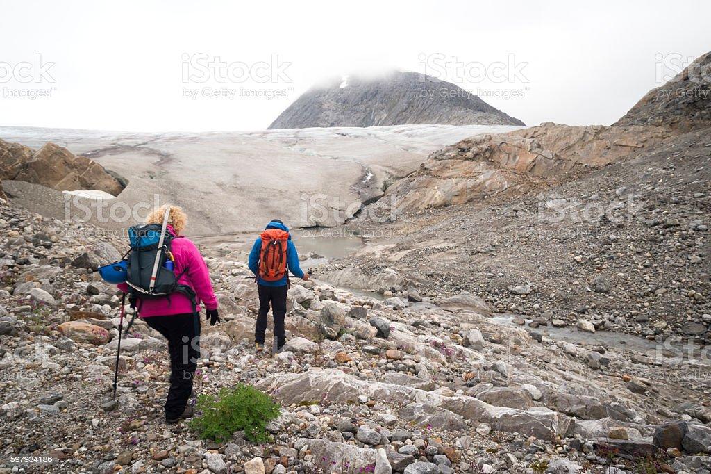 Two people hike over moraine toward glacier stock photo