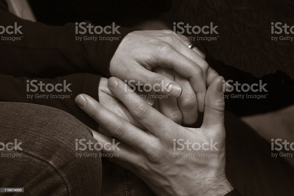 Two people holding each other's hands in hope royalty-free stock photo