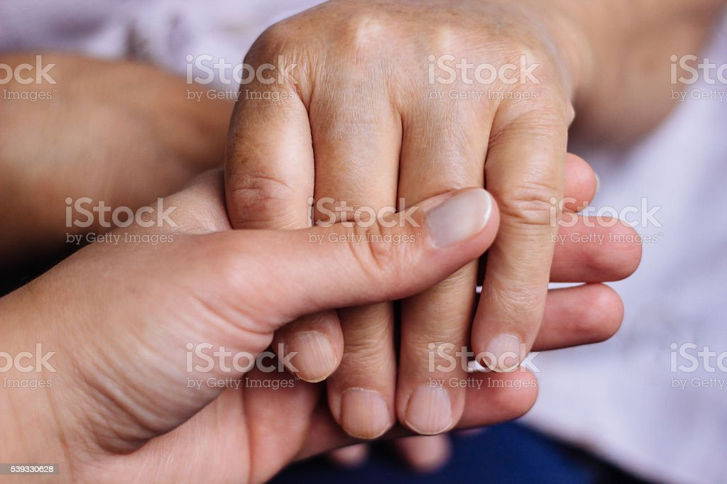 Two people holding each other's hands stock photo