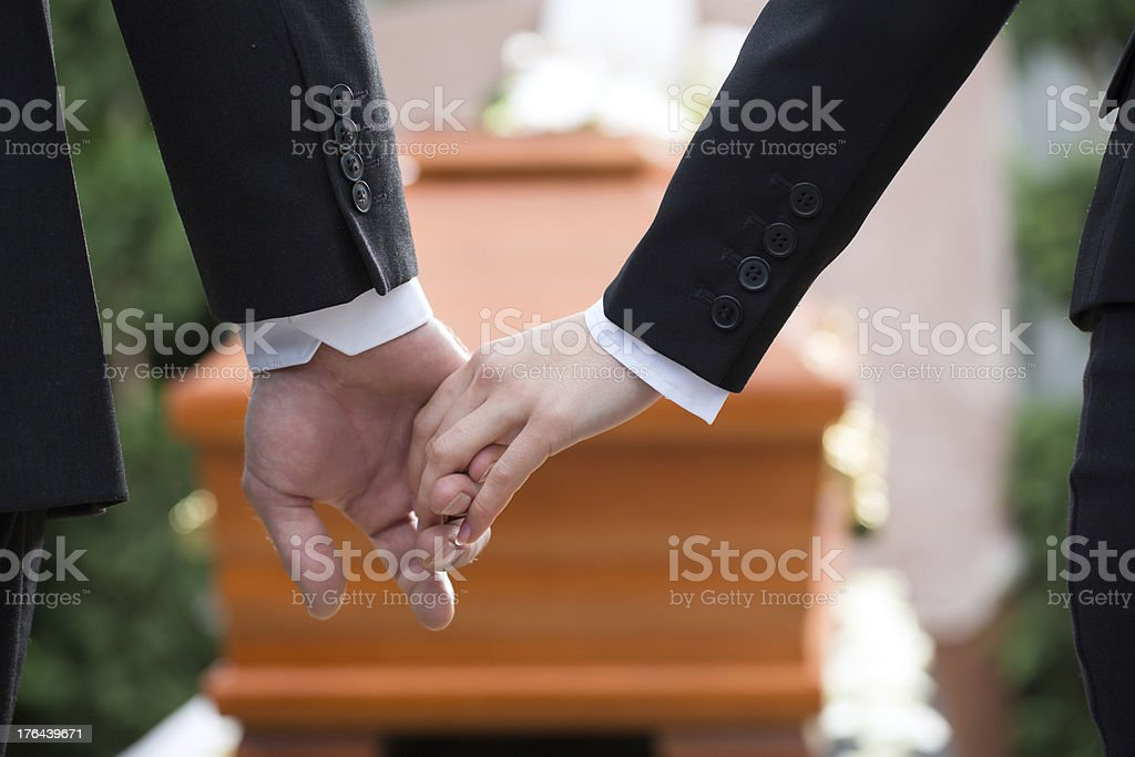 Two people holding hands at a funeral stock photo