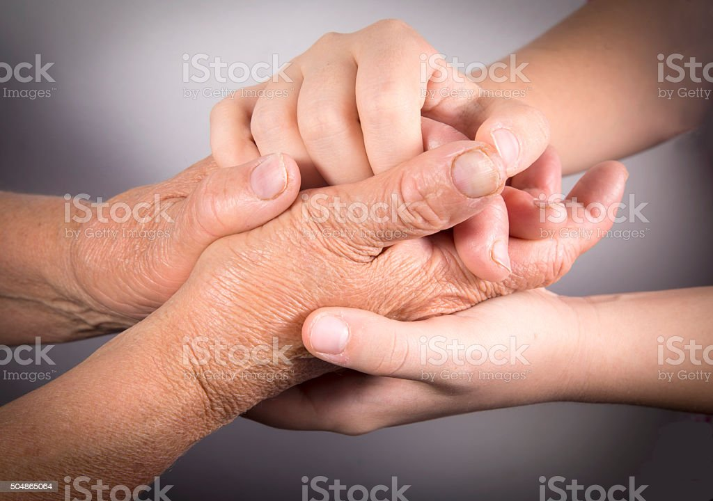 Two people holding hands for comfort stock photo