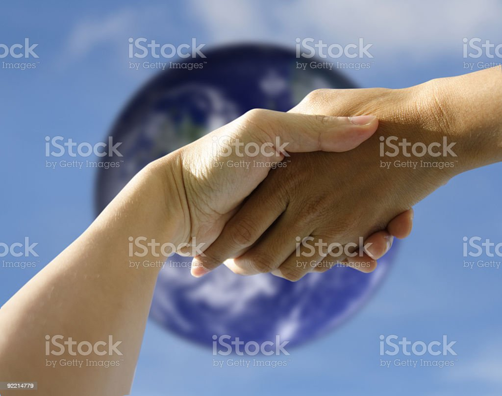 Two people holding hands with the Earth in the background stock photo