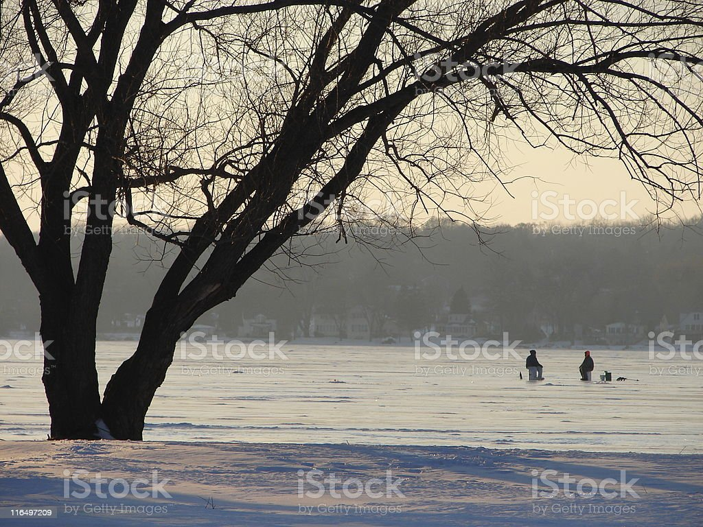 Two people ice fishing royalty-free stock photo