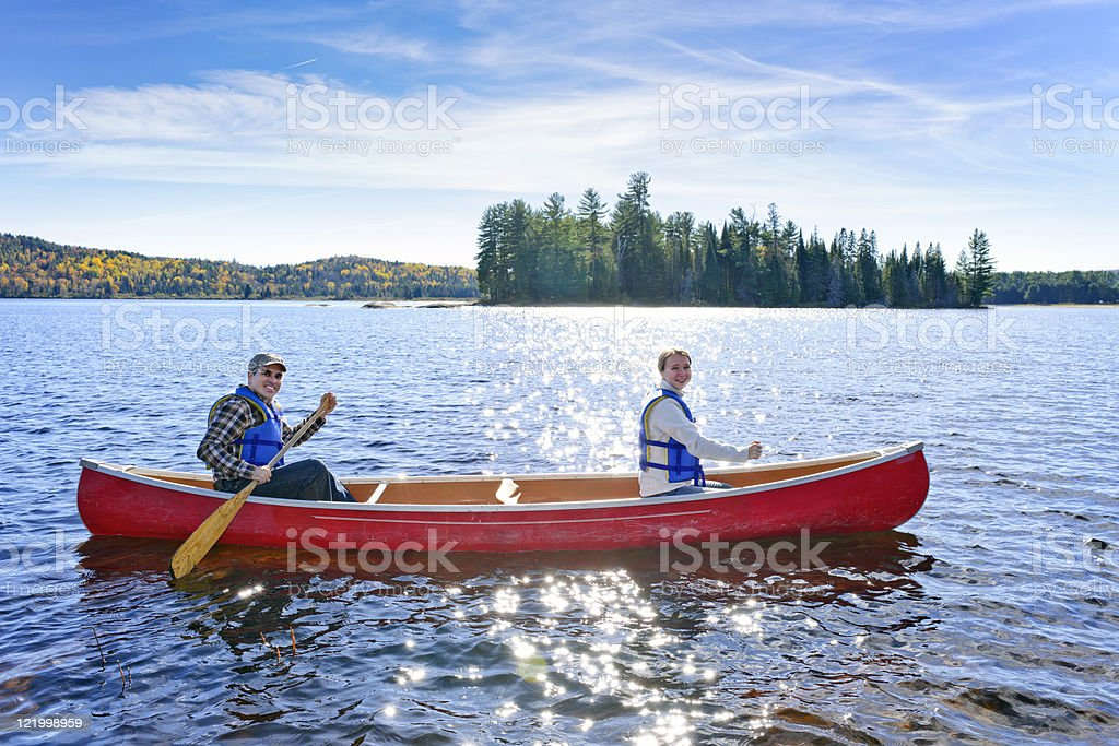 Two people in a red canoe on a lake stock photo