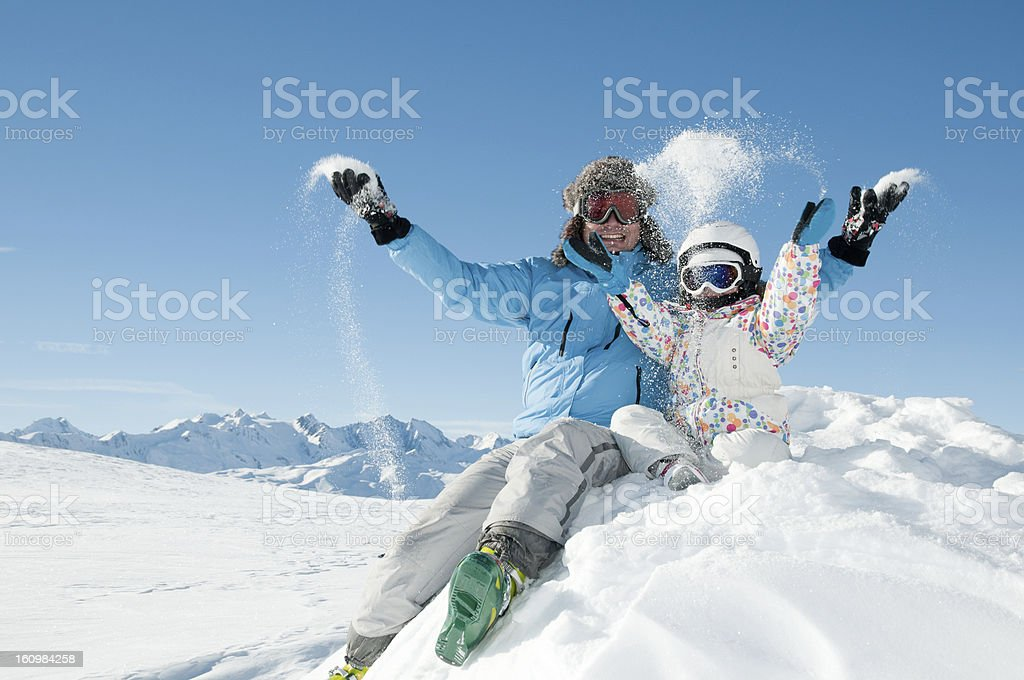 Two people in ski suits throwing snow into the air royalty-free stock photo