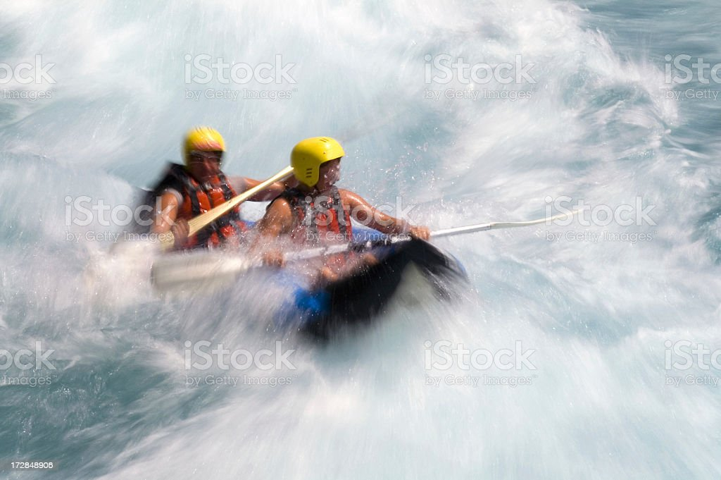 Two people in yellow helmets white water rafting stock photo