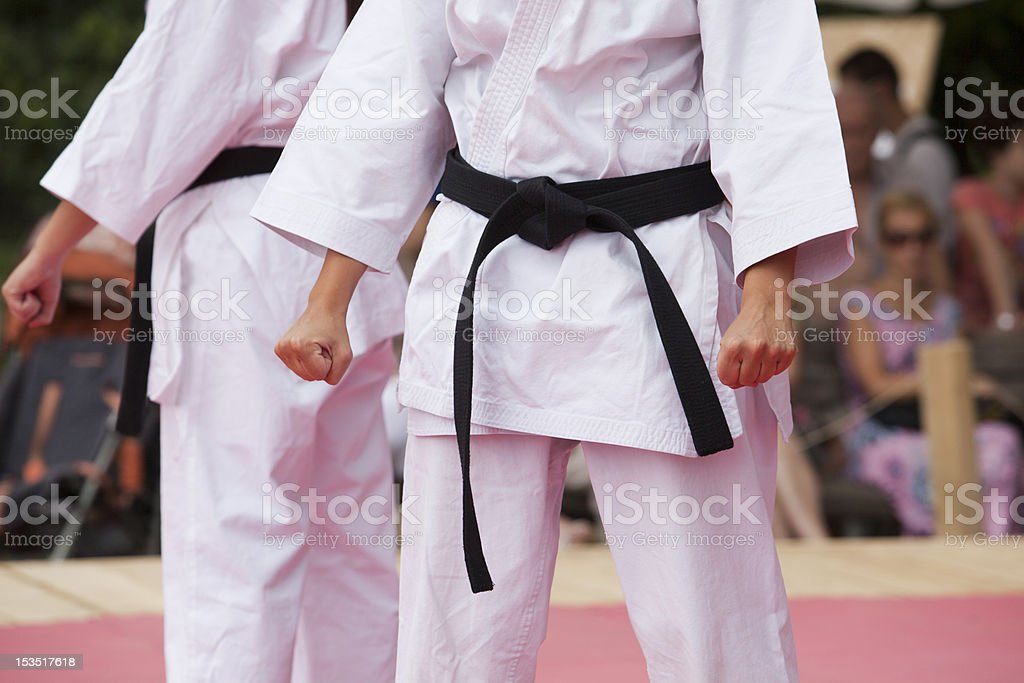 Two people is Karate uniforms with clenched fists on stage stock photo