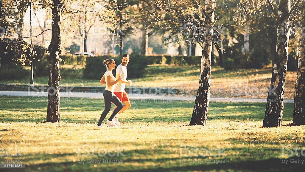 Two people jogging in park. stock photo