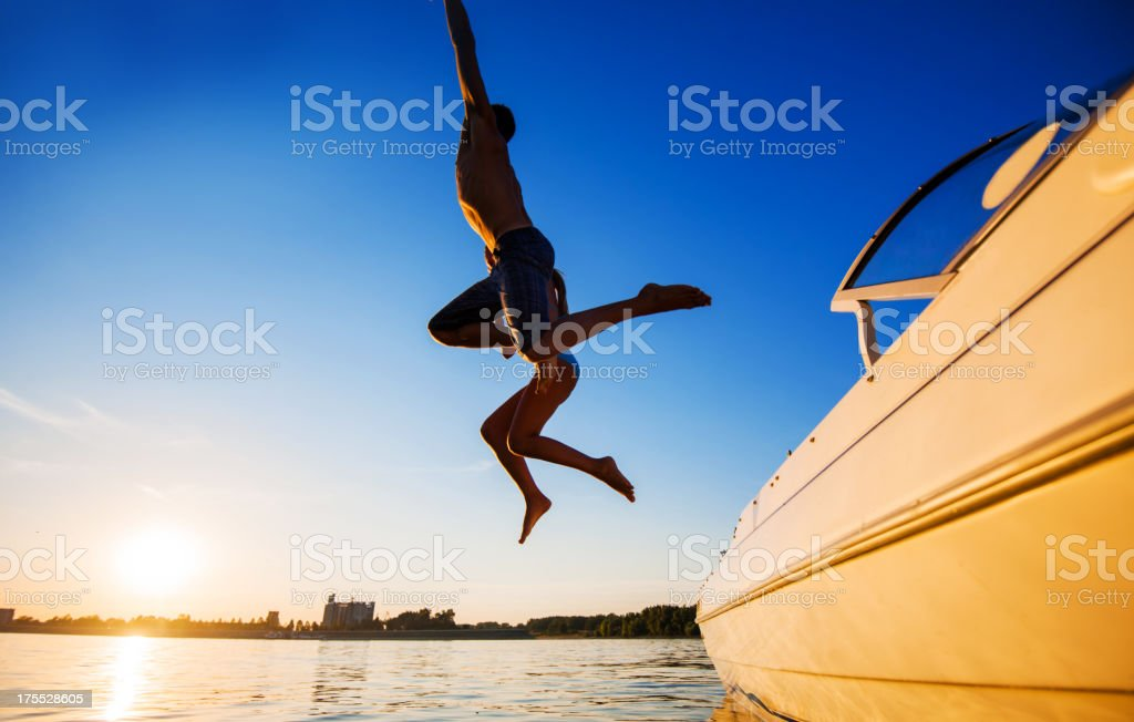 Two people jumping in water against the blue sky. stock photo